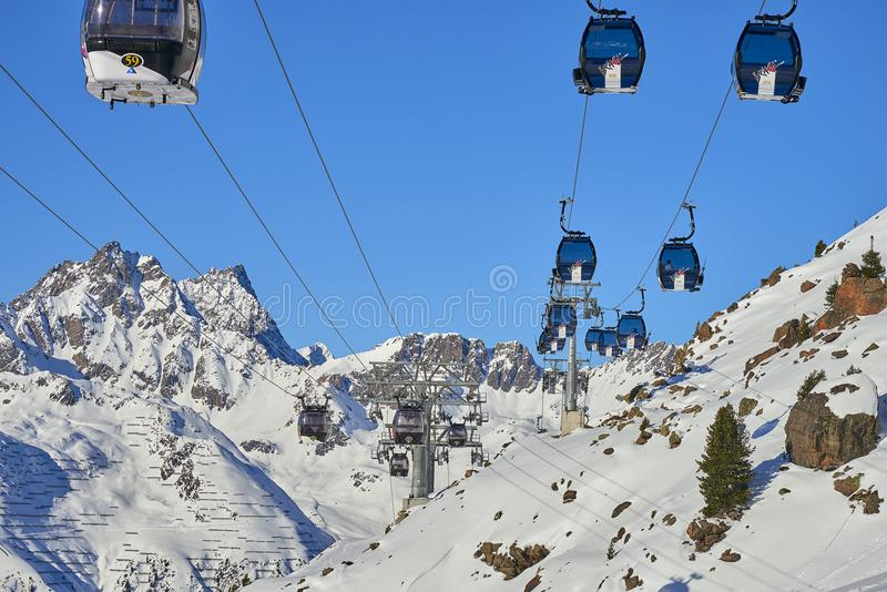 Two links of mono-cable detachable gondolas with high transport capacity lift skiers to the hill top in Tyrol Alps. royalty free stock images