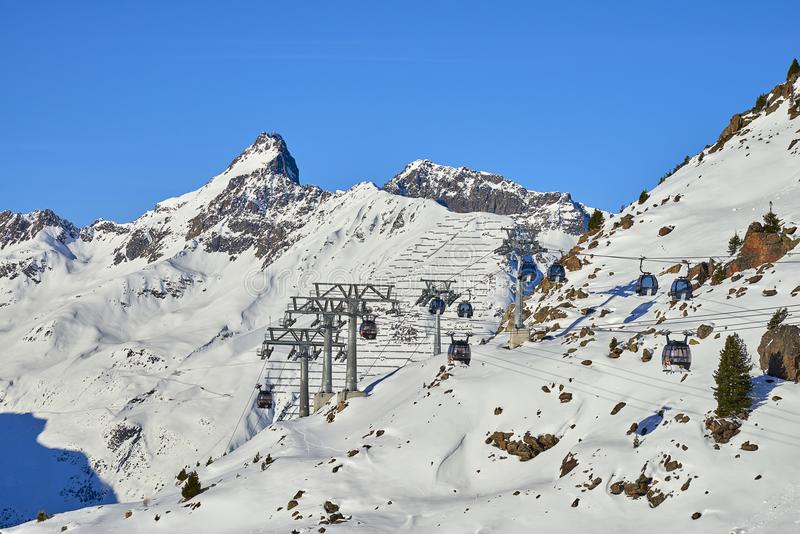 Two links of mono-cable detachable gondolas with high transport capacity lift skiers to the hill top in Tyrol Alps. royalty free stock photos