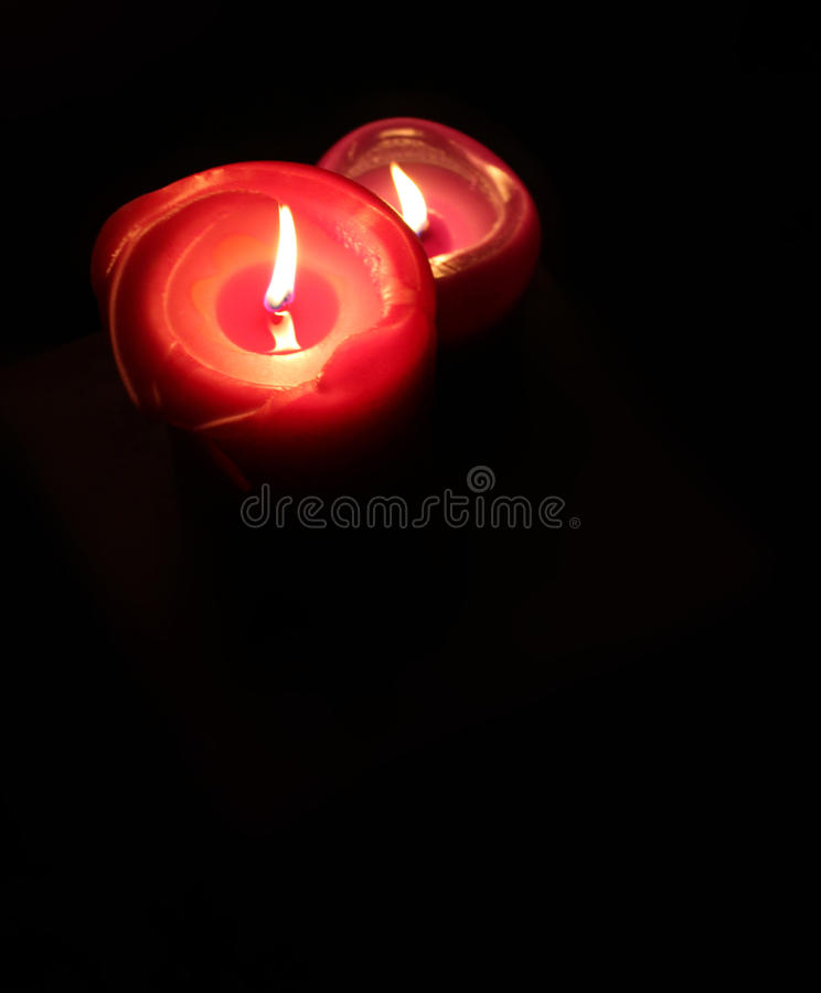 Two lit candles in the dark stock image