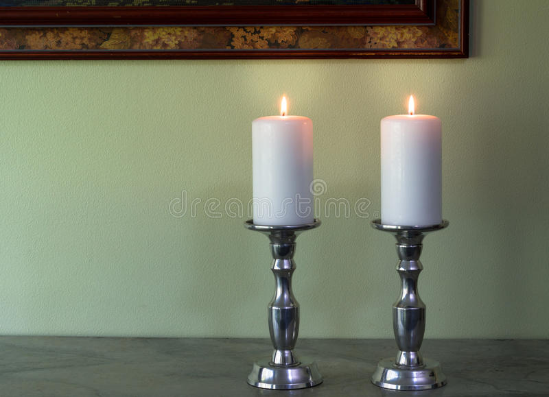 Two lit white candles in canelabra against green wall texture ba royalty free stock image