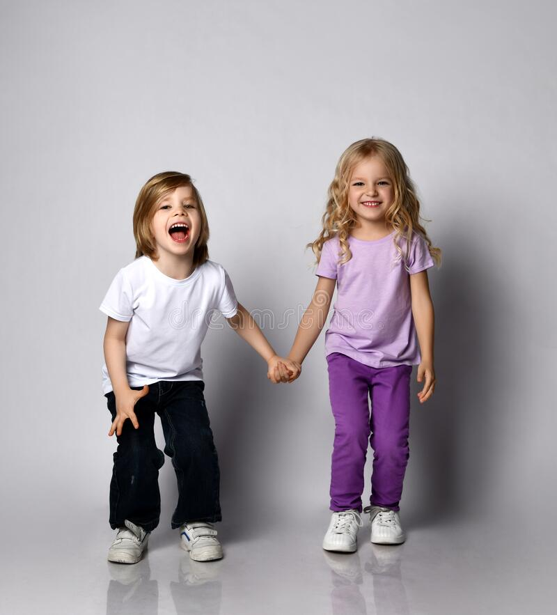 Free Two Little Active Blond Kids Holding Hands Girl And Boy In Stylish Casual Clothing Have Fun Jumping Screaming Royalty Free Stock Images - 179468249