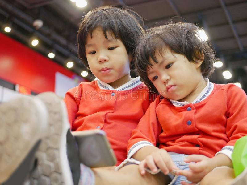Two little Asian baby girl, sisters, sitting and watching a smartphone together, while waiting for her mother to do some errands royalty free stock image
