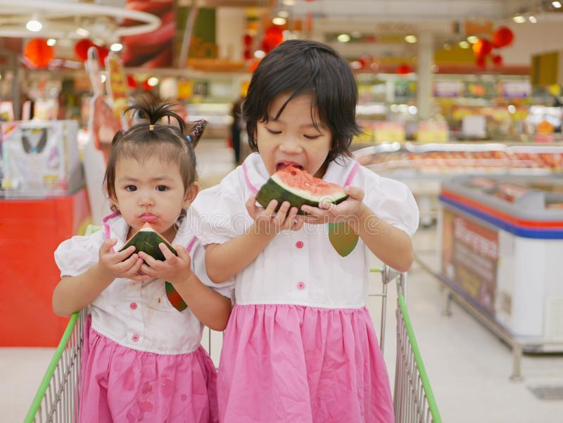Two little Asian baby girls, siblings, eating water melon in a supermarket in a shopping cart royalty free stock image