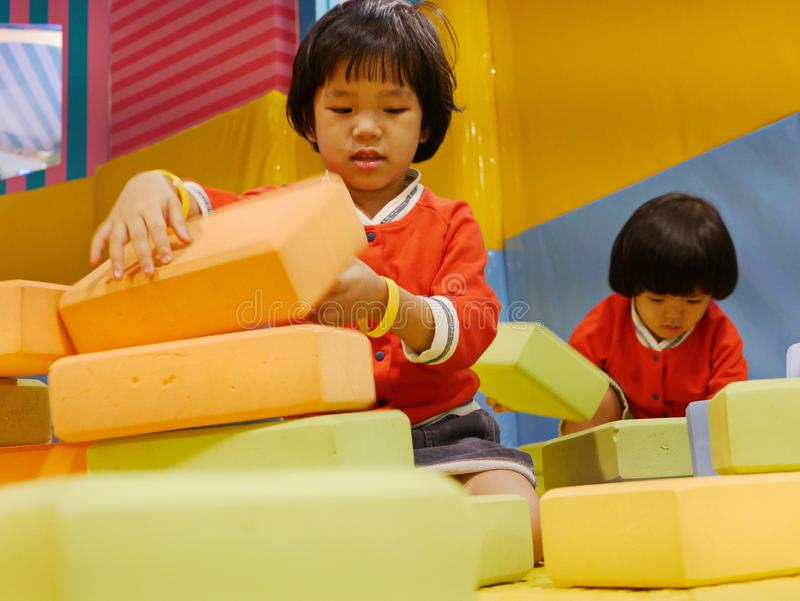 Two little Asian baby girls, sisters, stacking up foam building bricks / blocks together at an indoor playground. Playing foam blocks helps develop children`s royalty free stock photography