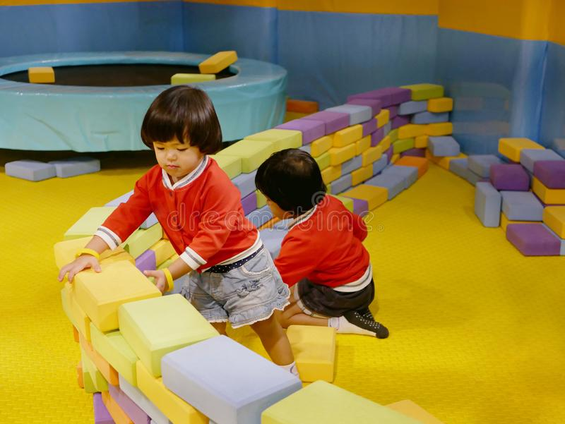 Two little Asian baby girls, sisters, stacking up foam building bricks / blocks together at an indoor playground. Playing foam blocks helps develop children`s royalty free stock images