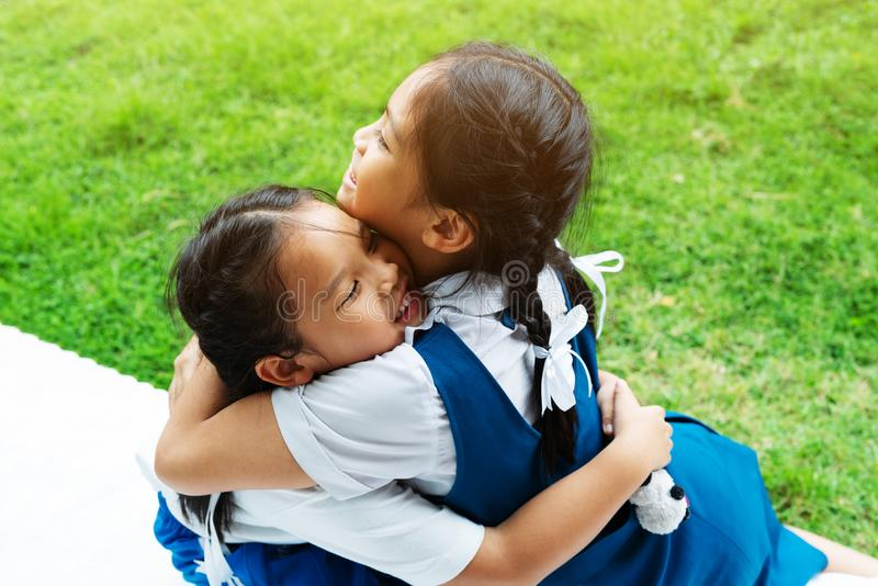 Two little asian girls sisters hugging happy post in school uniform, back to school concept royalty free stock image