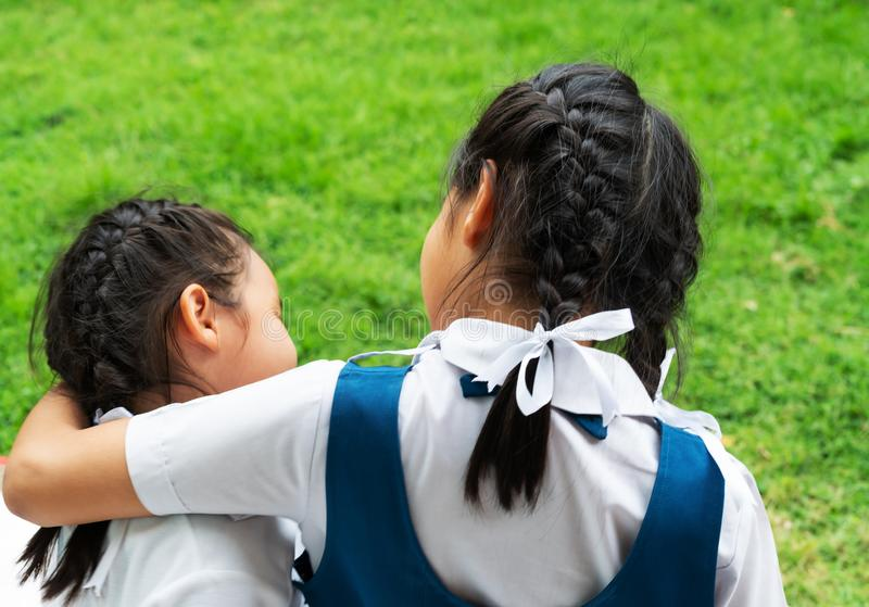 Two little asian girls sisters hugging happy post in school uniform, back to school concept royalty free stock photography