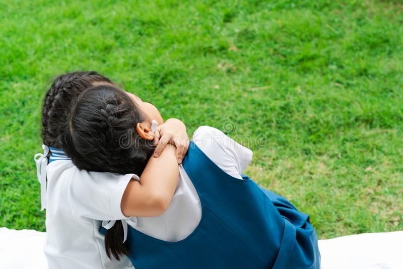 Two little asian girls sisters hugging happy post in school uniform, back to school concept stock photos