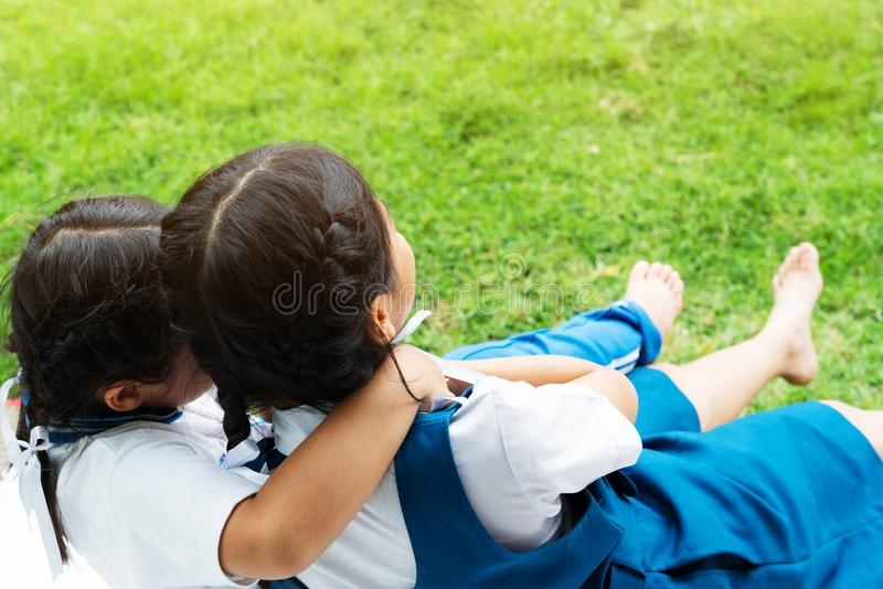 Two little asian girls sisters hugging happy post in school uniform, back to school concept royalty free stock images