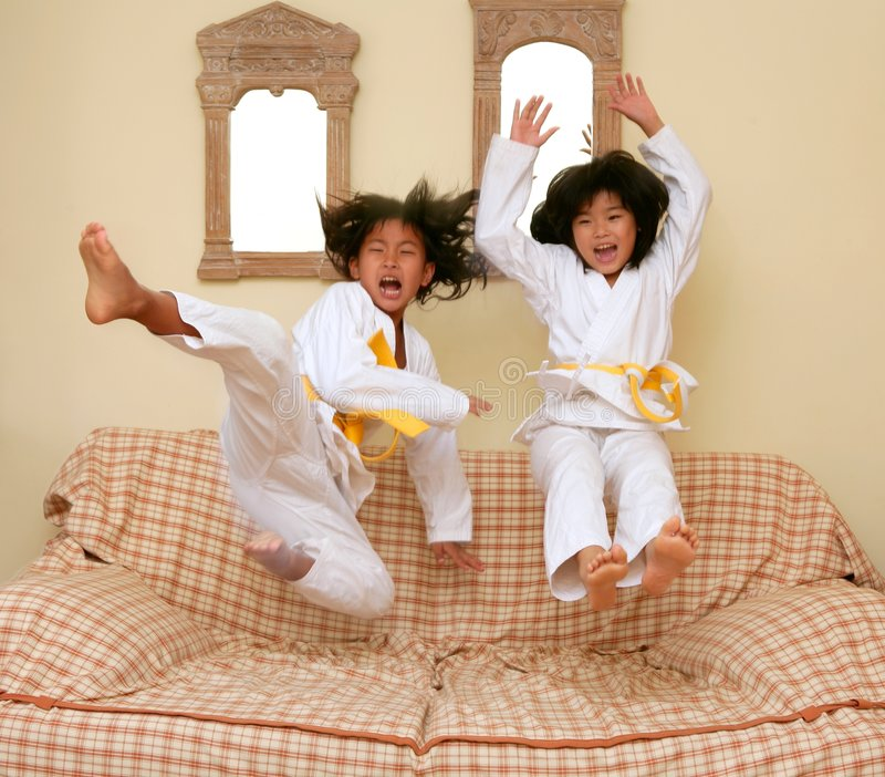 Download Two Little Asian Judo Gils Jump On Sofa Royalty Free Stock Photography - Image: 8828027