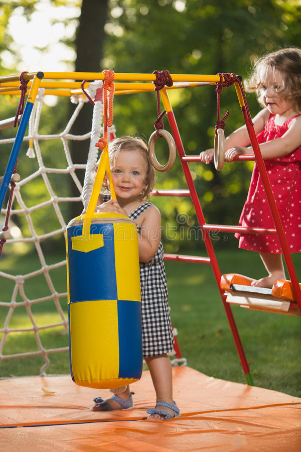 The two little baby girls playing at outdoor playground stock photography