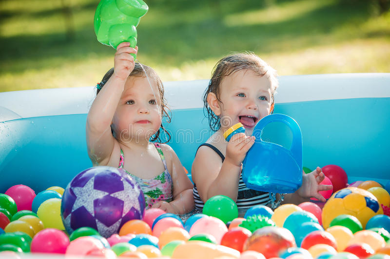 The two little baby girls playing with toys in inflatable pool in the summer sunny day stock photo