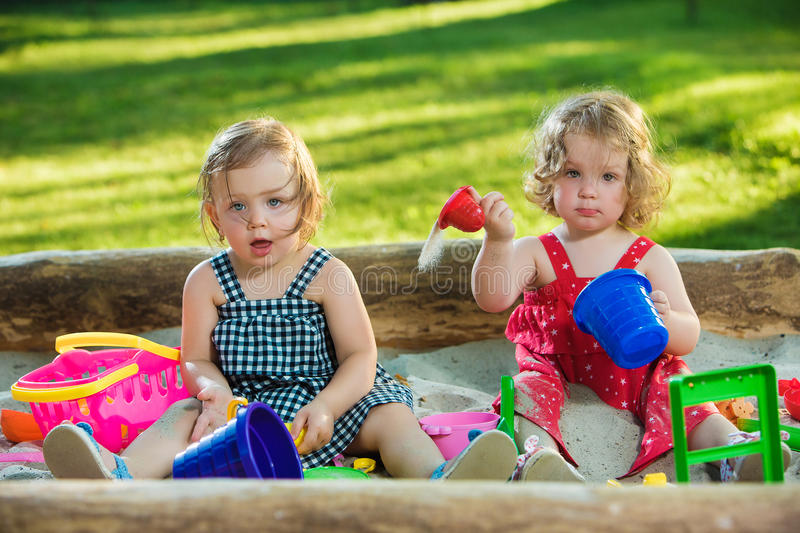 The two little baby girls playing toys in sand stock photography
