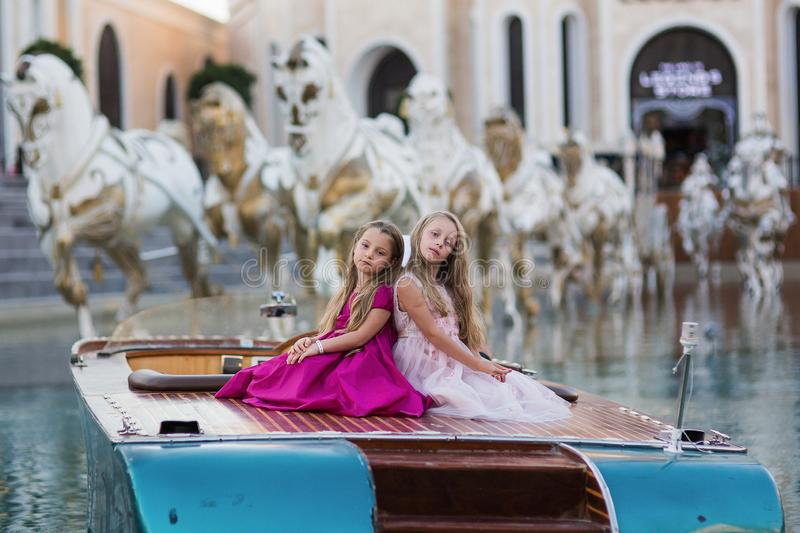 Two little beautiful girls in lush fashionable dresses sit on a boat on vacation. Girls posing royalty free stock photos
