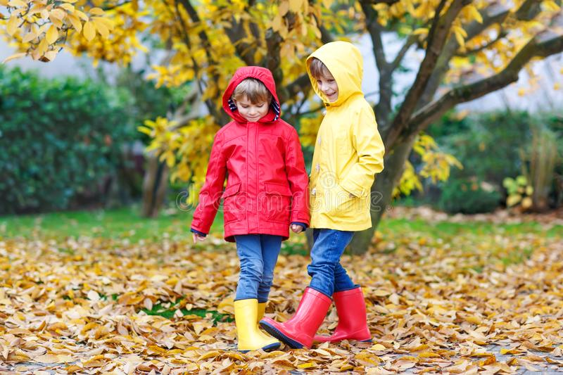 Two little best friends and kids boys autumn park in colorful clothes. Happy siblings children having fun in red and stock photos
