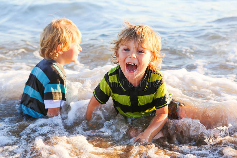 Two little blond kid boys having fun with wave royalty free stock images