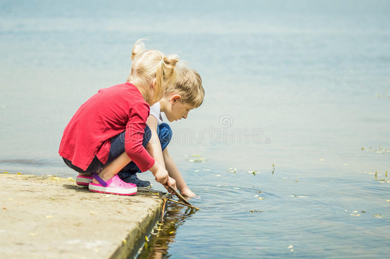 Two little blonde kids, boy and girl, sitting on a pier on a lake or river and searching for something or fishing with wooden. Stick. Friendship, summer royalty free stock images