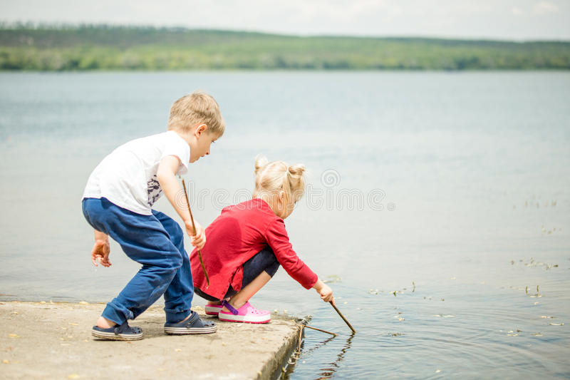 Two little blonde kids, boy and girl, sitting on a pier on a lake or river and searching for something or fishing with wooden royalty free stock photo