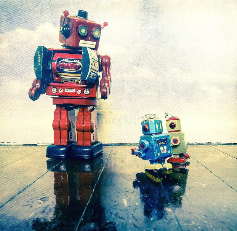 Two little bots being reprimanded. By the big red robot boss stock photos