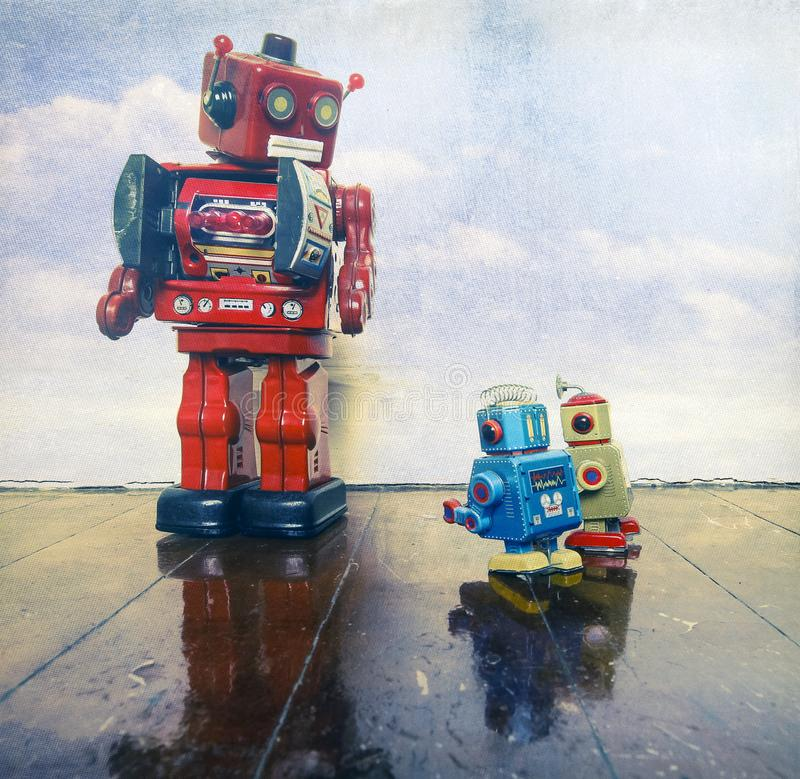 Two little bots being reprimanded. By the big red robot boss stock images