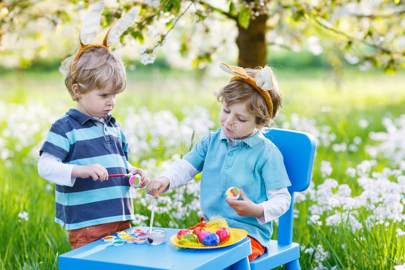 Two little boy friends in Easter bunny ears coloring eggs royalty free stock photography