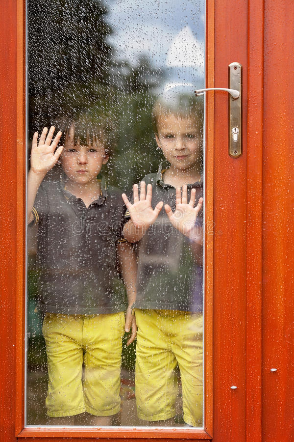 Two little boy, wearing same clothes looking through a big glass stock photography