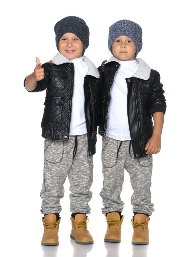 Two little boys in black jackets and hats. royalty free stock images