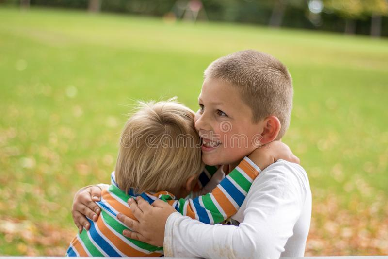 Two little boys brtohers holding around the shoulders in sunny summer day. Brother love. Concept friendship royalty free stock image