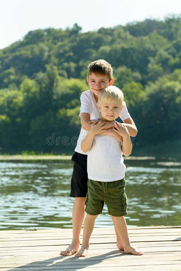 Two little boys are embracing on the bank of the river. Concept of friendship and fraternity.  royalty free stock image