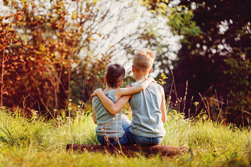Two little boys friends hug each other in summer sunny day. Brother love. Concept friendship. Back view stock photo