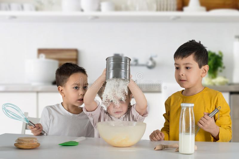 Two little boys and girl cook cake in kitchen. The girl sifts the flour through a sieve, the boys watch the process with interest stock photography