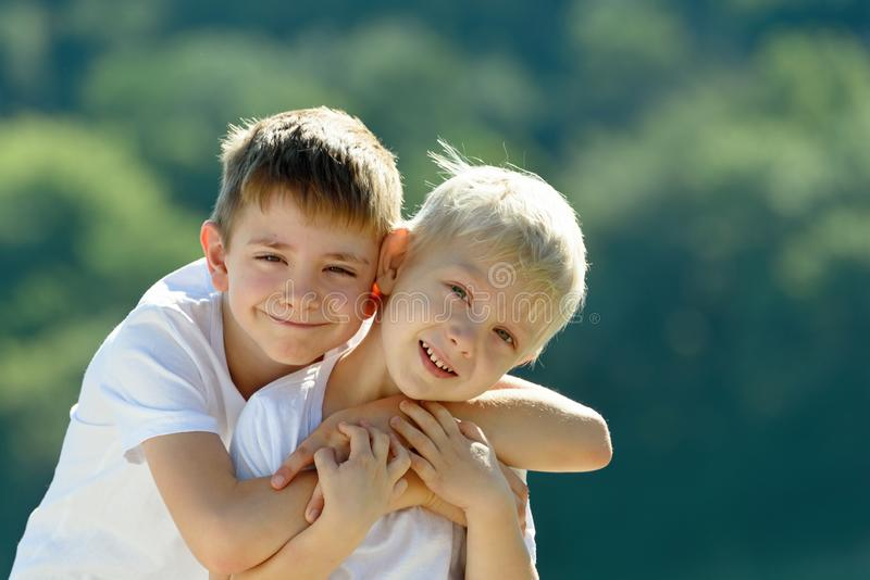 Two little boys are hugging outdoors. Concept of friendship and fraternity.  stock photos