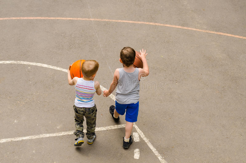 Two little boys playing on a basketball court royalty free stock photos