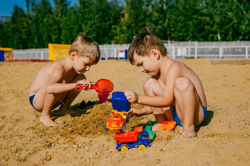 Two little boys playing with cars on a sandy beach stock photo