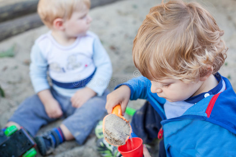 Two little boys playing with sand in summer stock images