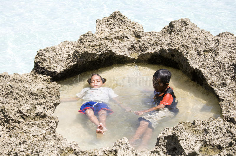 Two little boys are relaxing on Boracay beach stock image