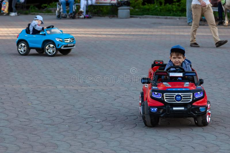 Two little boys ride on red and blue electric cars while walking with their parents in a city park with green trees, laughing and stock image