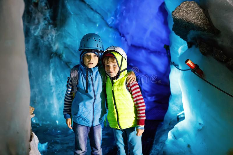 Two little boys with safety helmets and clothing with mountains landscape backgrounds. Kids hiking and discovering stock photography