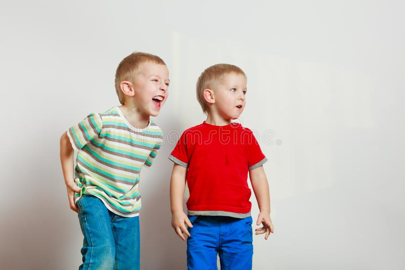 Two little boys siblings playing together on table stock images