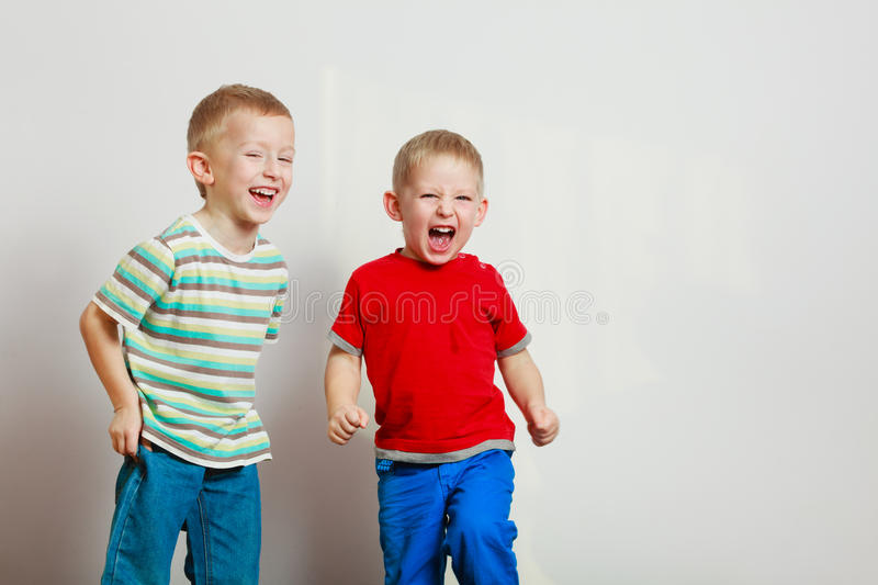 Two little boys siblings playing together on table stock image