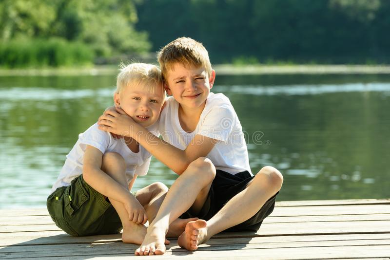 Two little boys sit in an embrace on the banks of the river. Concept of friendship and fraternity.  stock photography