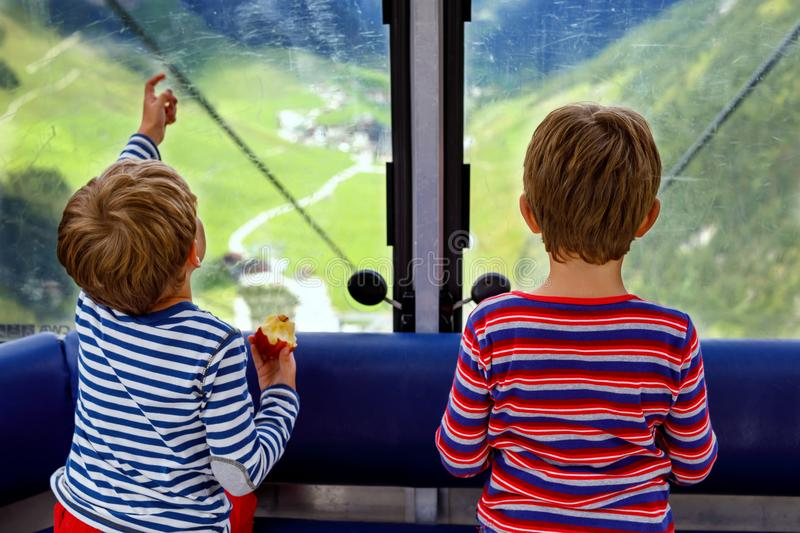 Two little boys sitting inside of cabin of cable car and looking on mountains landscape. stock photos