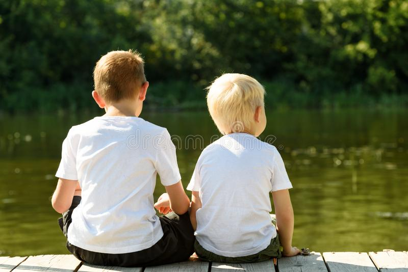 Two little boys are sitting on the pier on the river bank. Concept of friendship and fraternity. Back view.  stock photos