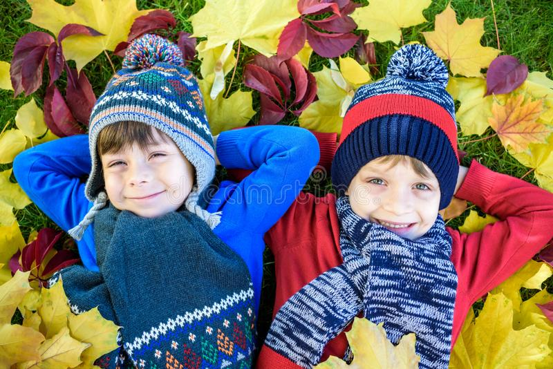 Two little brother kids boys lying in autumn leaves in colorful casual clothing. Happy siblings having fun in autumn park on warm royalty free stock images