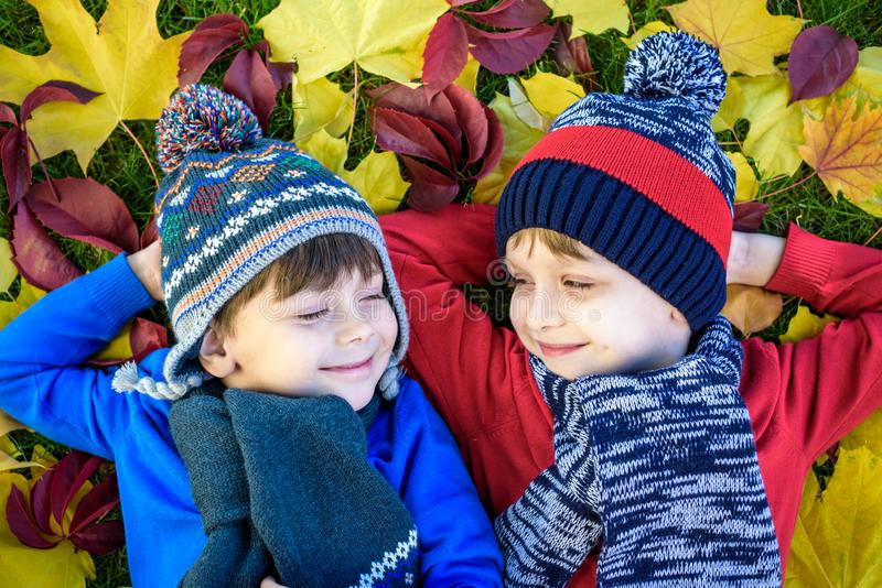 Two little brother kids boys lying in autumn leaves in colorful casual clothing. Happy siblings having fun in autumn park on warm royalty free stock image