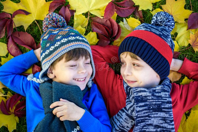 Two little brother kids boys lying in autumn leaves in colorful casual clothing. Happy siblings having fun in autumn park on warm royalty free stock photo