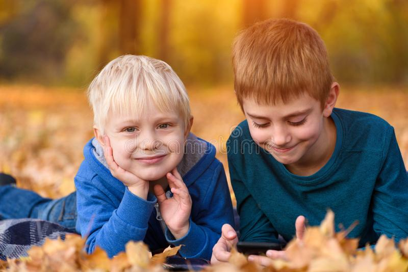 Two little brothers lying in yellow autumn leaves. Smiling and having fun. Fall day stock photos