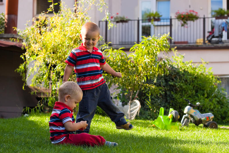 Two little brothers play outdoors royalty free stock image