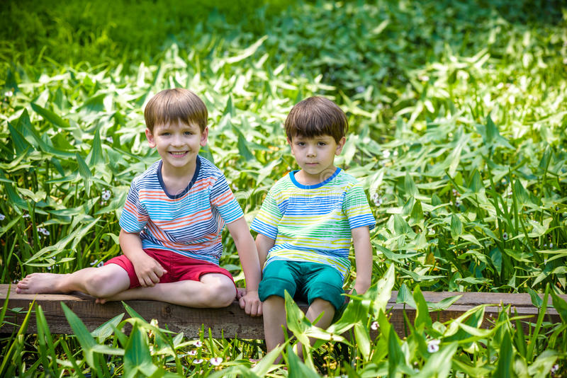 Two little brothers playing with paper boats by a river on warm and sunny summer day. Two little sibling brothers playing with paper boats in a river or lake on royalty free stock photo