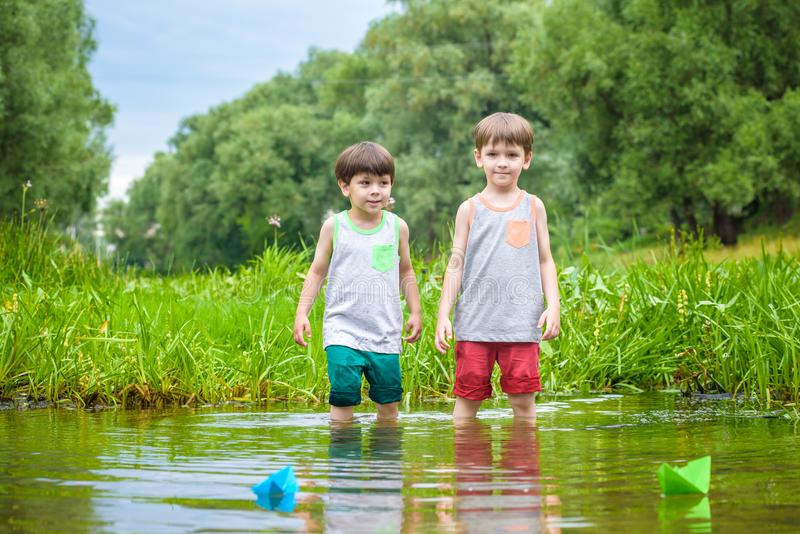 Two little brothers playing with paper boats by a river on warm and sunny summer day. Two little sibling brothers playing with paper boats in a river or lake on royalty free stock images